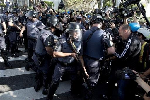 Policiais discutem com jornalistas que cobrem prisão de um manifestante