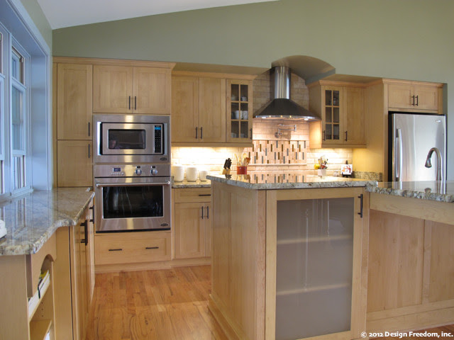 Kitchen with stainless steel appliances and light wood ...