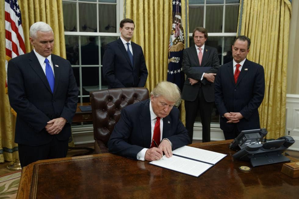 Trump, este viernes, firmando su primer decreto en el Despacho Oval flanqueado por su vicepresidente y jefe de gabinete