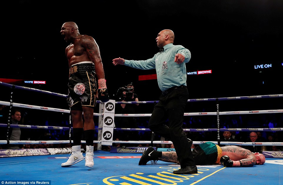 An ectastic Whyte celebrates his comfortable victory while Browne lays unmoving on the canvas