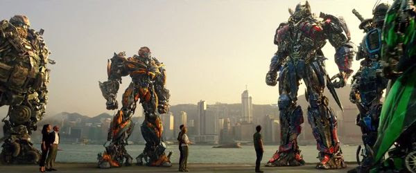 Optimus Prime and his fellow Autobots confer with Cade Yeager (Mark Wahlberg) and his fellow humans in TRANSFORMERS: AGE OF EXTINCTION.