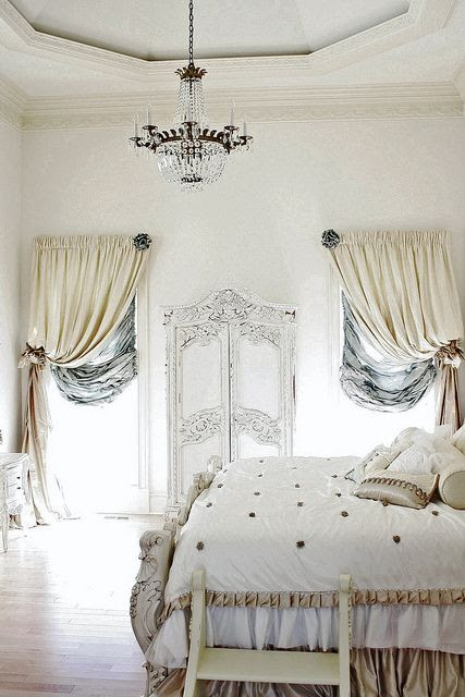 Romantic French cottage bedroom; small step up to the bed, lovely chandelier, ornate moulding around door, rich fabrics curtains.