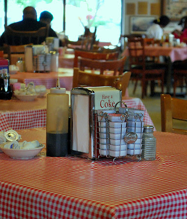 Table setting featuring a container of molasses and vintage Coke napkin dispensers.