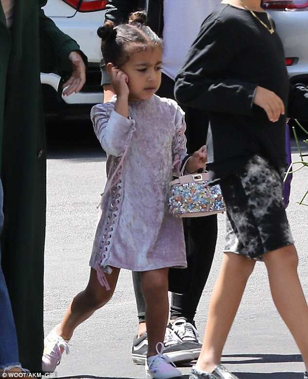 Chic: Kim Kardashian and Kanye West's daughter North is naturally inclined to steal some designer style, as illustrated on Sunday when she headed to church with her aunt Kourtney alongside cousins Mason, seven and Penelope, four