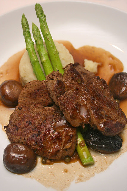 Filet of beef with piquant green peppercorn sauce, served with mound of creamy whipped potatoes and sauteed crimini mushrooms