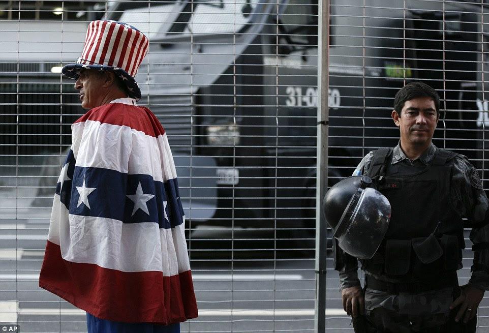 Aqui para o esporte: Um ventilador da equipe dos EUA fez o seu caminho para o Maracanã passado um policial brasileiro equipado-motim e na frente de um dos canhões de água sendo mantidos em reserva em caso de distúrbio