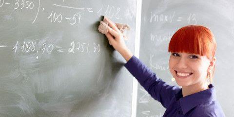 En la imagen se muestra a una chica explicando en la pizarra a sus alumnos la medicion de la felicidad