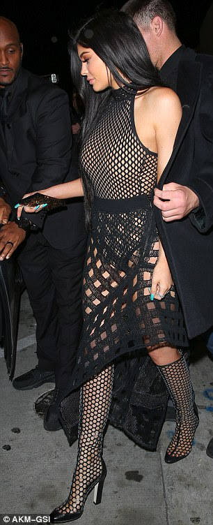 All about that bass: She complemented the daring one-piece with an equally racy high-waisted mesh pencil skirt that hugged her pert derriere and hips as she left the venue