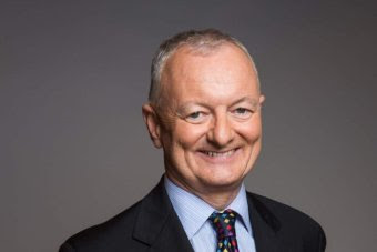 ABC election expert Antony Green smiles at the camera with his hands clasped behind his back.