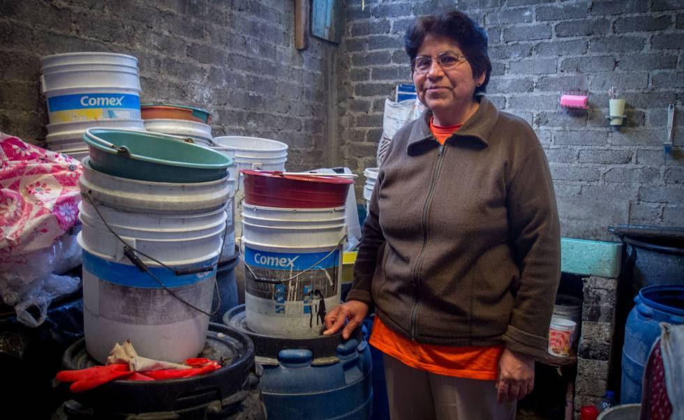Una mujer con los cubos que usa para recoger agua de lluvia.