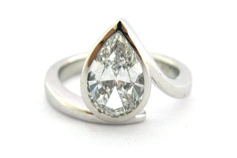 Bezel set pear shape diamond ring with a twisted band