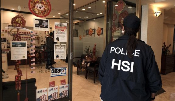A police officer enters California Investment Immigration Fund in San Gabriel, Calif., Wednesday, April 5, 2017. Federal authorities on Wednesday raided the Los Angeles-area business they say cheated a U.S. government visa program to obtain green cards for wealthy Chinese investors. (AP Photo/Rich Vogel