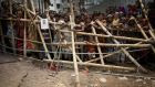 Curious onlookers and relatives of missing victims watch from behind a makeshift fence as workers start dislodging parts of the garment factory building which collapsed in Savar, near Dhaka, Bangladesh. Photograph: Wong Maye-E/AP