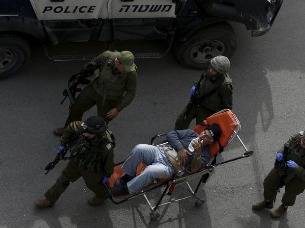 Soldados israelenses retiram palestino ferido de local onde uma mulher palestina foi morta após ter tentado esfaquear um militar israelense em Hebron  (Foto: Mussa Qawasma/Reuters)