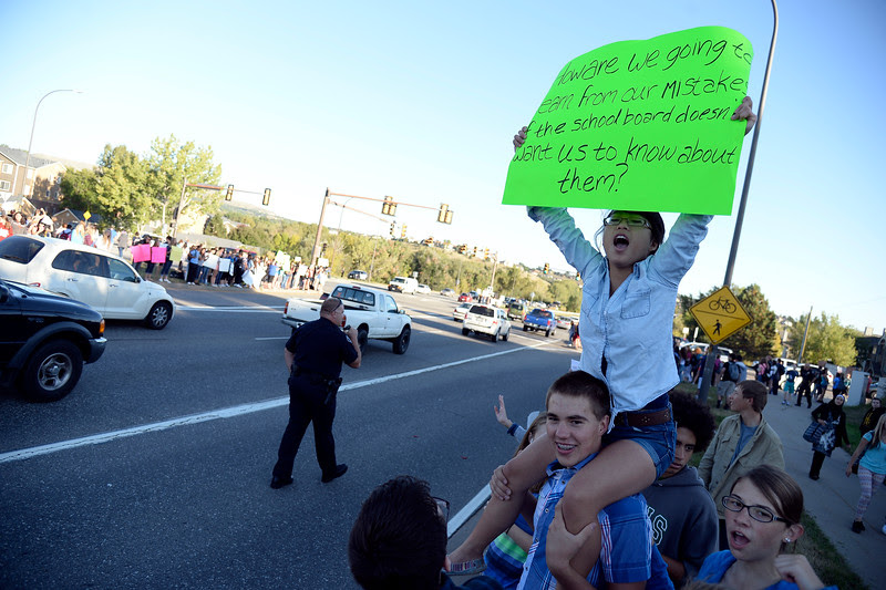 Josh Schroeder 10th grader holds Laura Studley, 10th grader on his shoulders as she holds up her sign during Bear Creek High School students walk out September 25, 2014 to protest proposed AP History changes as they lined Kipling St. in Lakewood. (Photo by John Leyba/The Denver Post)