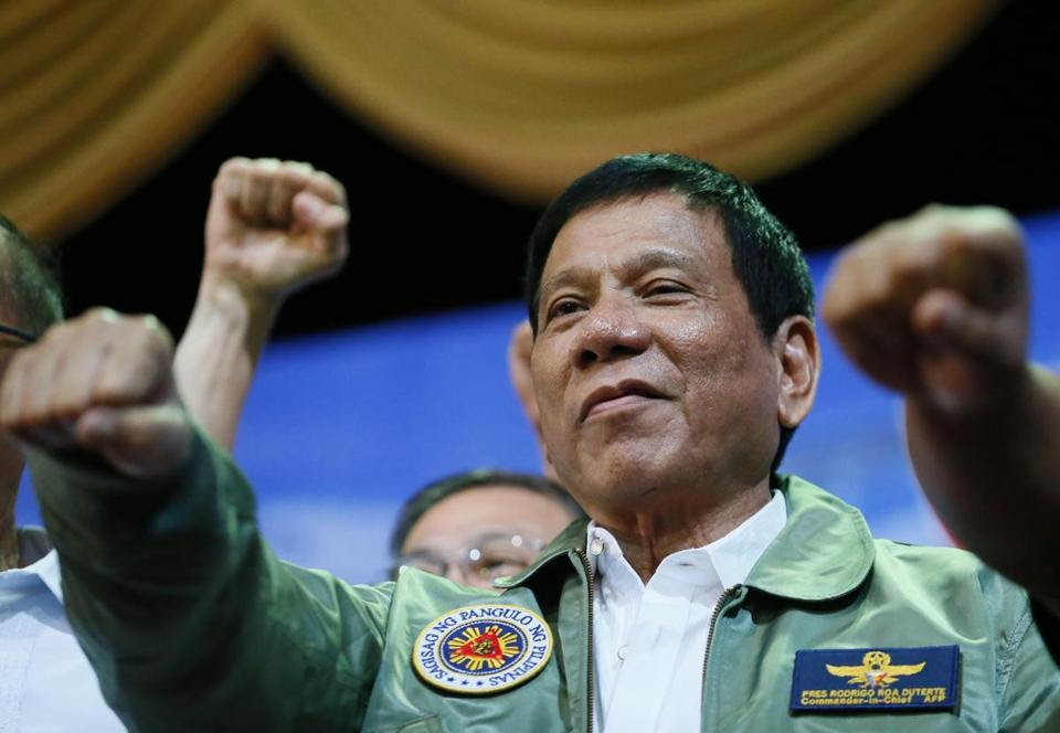 """Philippine President Rodrigo Duterte poses with a fist bump during his """"Talk with the Airmen"""" on the anniversary of the 205th Presidential Airlift Wing Tuesday, Sept. 13, 2016 at the Philippine Air Force headquarters in suburban Pasay city, southeast of Manila, Philippines. On Monday, President Duterte, in his first public statement opposing the presence of American troops, said he wants U.S. forces out of his country's south and blamed the United States for inflaming Muslim insurgencies in the region. (AP Photo/Bullit Marquez)"""