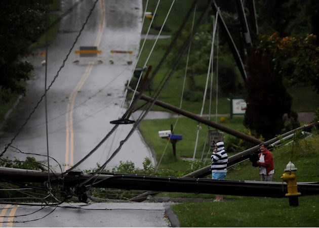 Residents on Foster Street in South Windsor, Conn., look over the mess of wires and down utility poles that were brought down during Irene, the hurricane that weakened to a tropical storm, Sunday, Aug