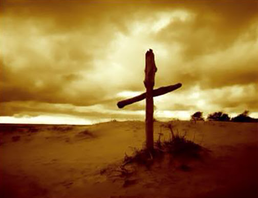 [Photo of a cross in the desert during a sunrise]