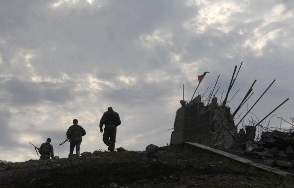 Separatistas pró-russos andar em um memorial de guerra destruído em Savur-Mohyla, a leste do monte da cidade de Donetsk, 28 de agosto de 2014 REUTERS / Maxim Shemetov