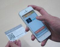 写真1 専用アプリ「TakeOutLive」でQRコードを読み取っている様子。アプリはiPhone版とAndroid版を用意した