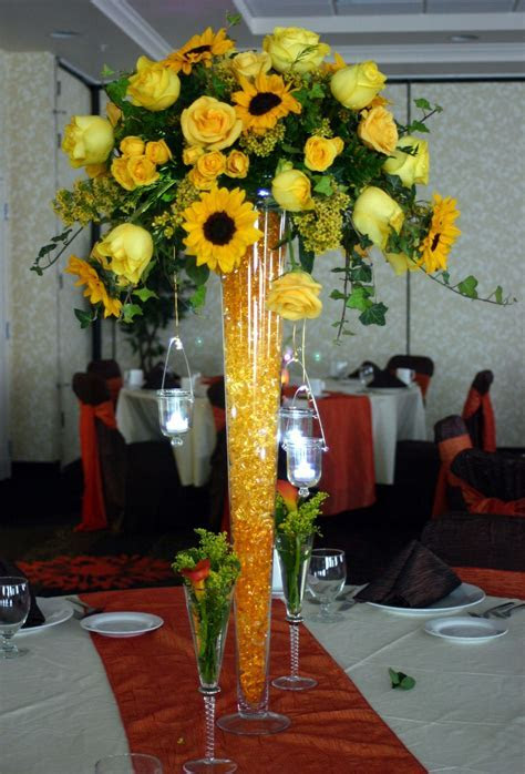 A monochromatic centerpiece features sunflowers, roses