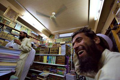 Man laughing in Islamic bookstore, Peshawar