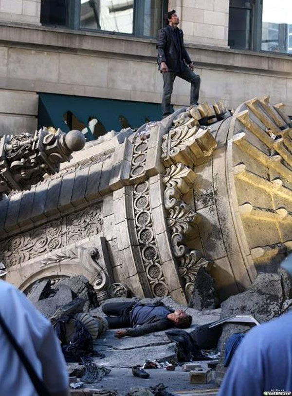 Shia LaBeouf lies unconscious on rubble as Patrick Dempsey stands triumphantly above him during filming of TRANSFORMERS 3.