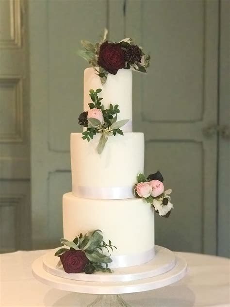 Tall and simple fondant cake dressed with fresh flowers
