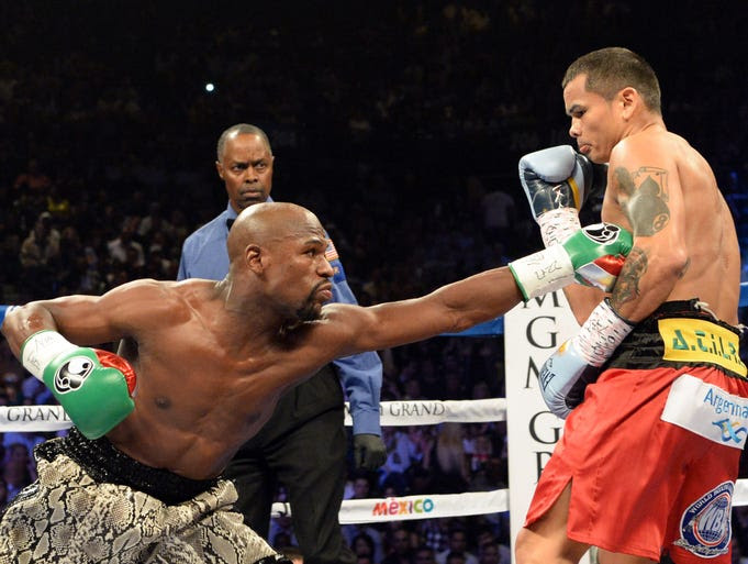 Mayweather reaches for Maidana in the early rounds.