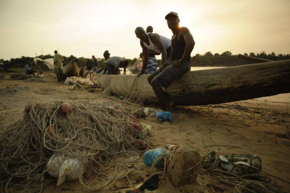 Unos pescadores arreglan las redes tras una jornada de pesca en Sierra Leona.