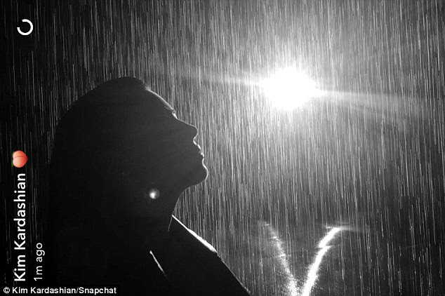 It's not even cloudy: Kim basked in the light of falling waetr in the museum's Rain Room