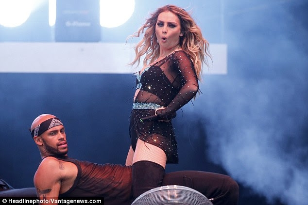 Standing tall: Perrie stood over one of the dancers as he reclined showing off his strong core