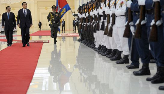 Cambodian Prime Minister Hun Sen and Thai Prime Minister Prayuth Chan-ocha walk past an honour guard upon Prayuth's arrival at the Peace Palace
