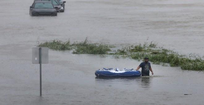 Un residente camina a través de las aguas durante la inundación de la tormenta tropical Harvey en Houston, Texas, EEUU.- REUTERS / Jonathan Bachman