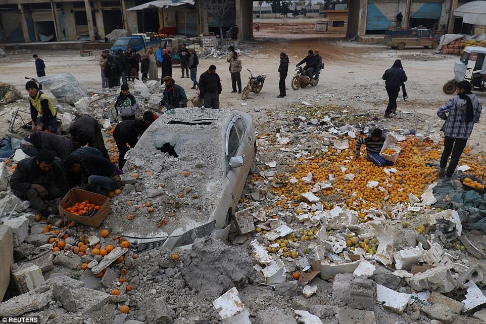 People collect scattered oranges strewn among the rubble created by an airstrike on a market on the rebel-held city Maarrat Misrin in Idlib province, Syria, on January 14