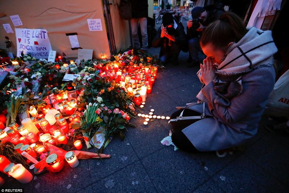 """Orações: Uma mulher reza ao lado de uma cruz de velas acesas no mercado de natal em Berlim perto de a mensagem """"a luz é mais forte do que a escuridão '"""