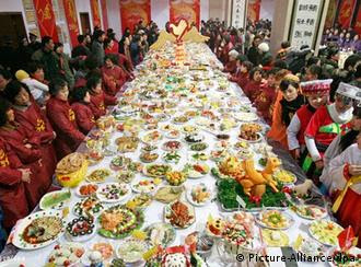 People look at dishes displayed on a large table during a dishes show event for the upcoming Chinese lunar New Year's Eve dinner in downtown Wuhan city, central China's Hubei province, 07 February 2010. More than 15,000 dishes were made by 9,048 families to celebrate the upcoming Chinese lunar New Year, also called Spring Festival which falls on 14 February, the first day of the 'Year of Tiger'. EPA/STR