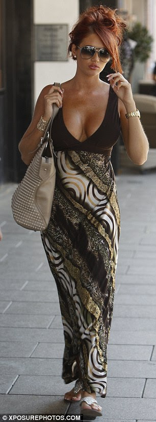 Taking the plunge: Reality TV star Amy Childs shows off her new DD cleavage in a brown maxi dress in Brentwood, Essex today