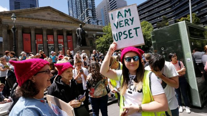 Woman holding sign saying 'I am very upset' as protesters take part in the Melbourne rally to protest against the Trump Inauguration on January 21, 2017