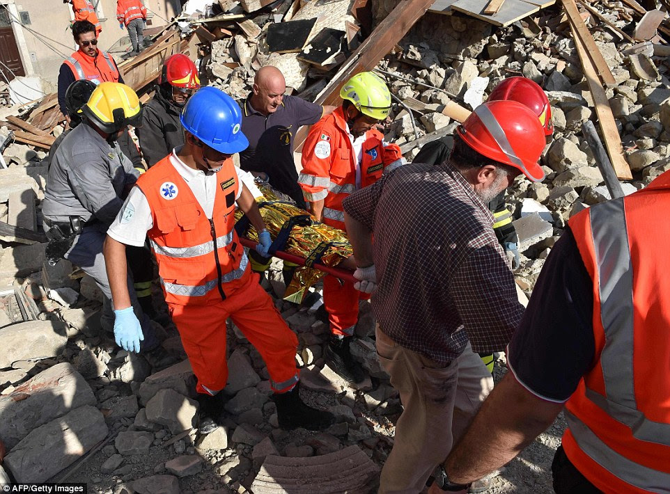 Rescuers carry a man on a stretcher among damaged buildings after a strong earthquake hit central Italy, in Arquata del Tronto