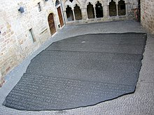 """Photo depicting a large copy of the Rosetta Stone filling an interior courtyard of a building in Figeac, France"""