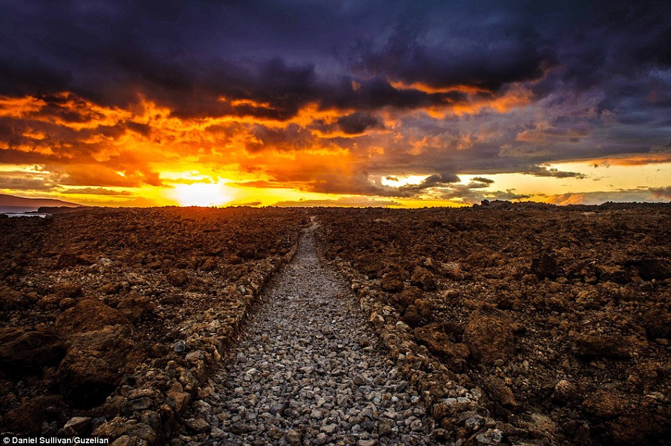 The sun spectacularly sets behind a preserved section of the King's Highway, a road of jagged stone built by King Pi'ilani in the 16th Century