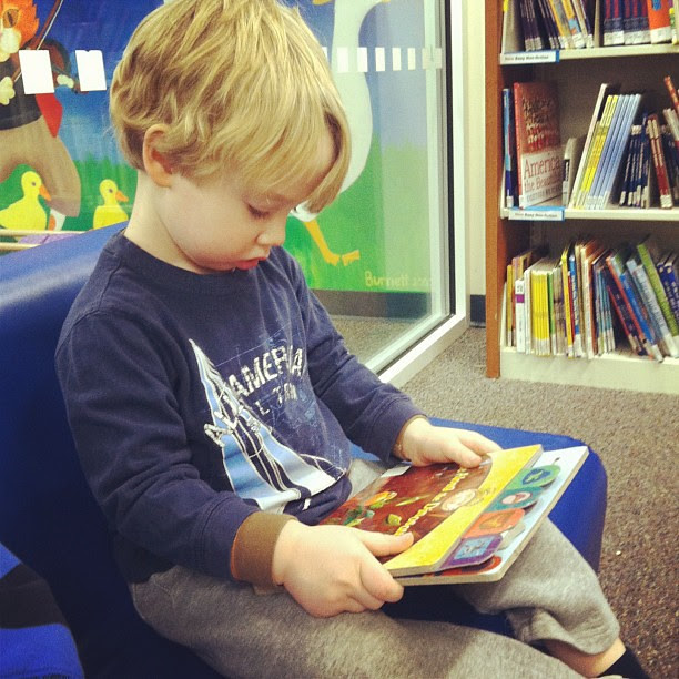 Looking at books for the 2 minutes he actually sat while we were at the library...