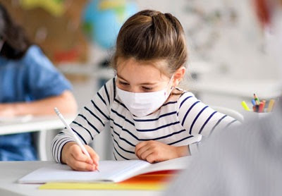 child with face mask at school writing