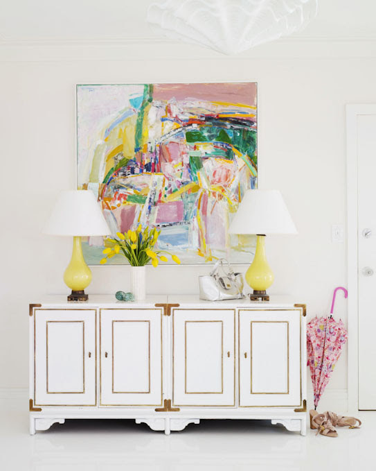 Fun, colorful foyer design with white vintage cabinet with campaign furniture hardware