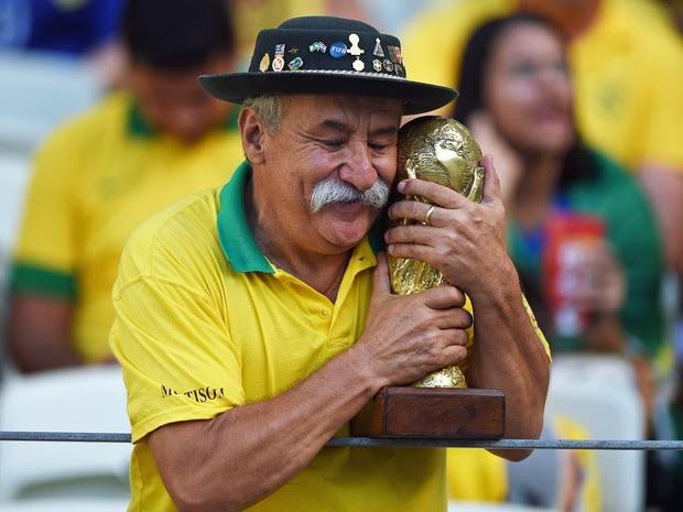 Torcedor conhecido como 'Gaúcho da Copa' abraça réplica da Copa do Mundo durante o jogo entre Brasil e Colômbia pela Copa em 4 de julho de 2014. Torcedor símbolo do Brasil em Copas do Mundo, Clóvis Acosta Fernandes morreu aos 60 anos em Porto Alegre (Foto: Eitan Abramovich/AFP/Arquivo)