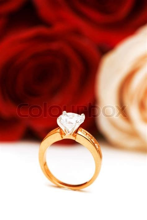 Engagement ring and roses at the background   Stock Photo