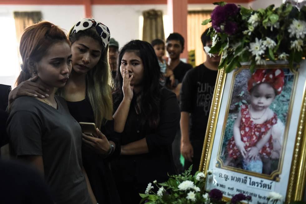 Jiranuch Trirat, de 22 años, consolada por sus amigos frente al retrato de su bebé, asesinada por su padre.