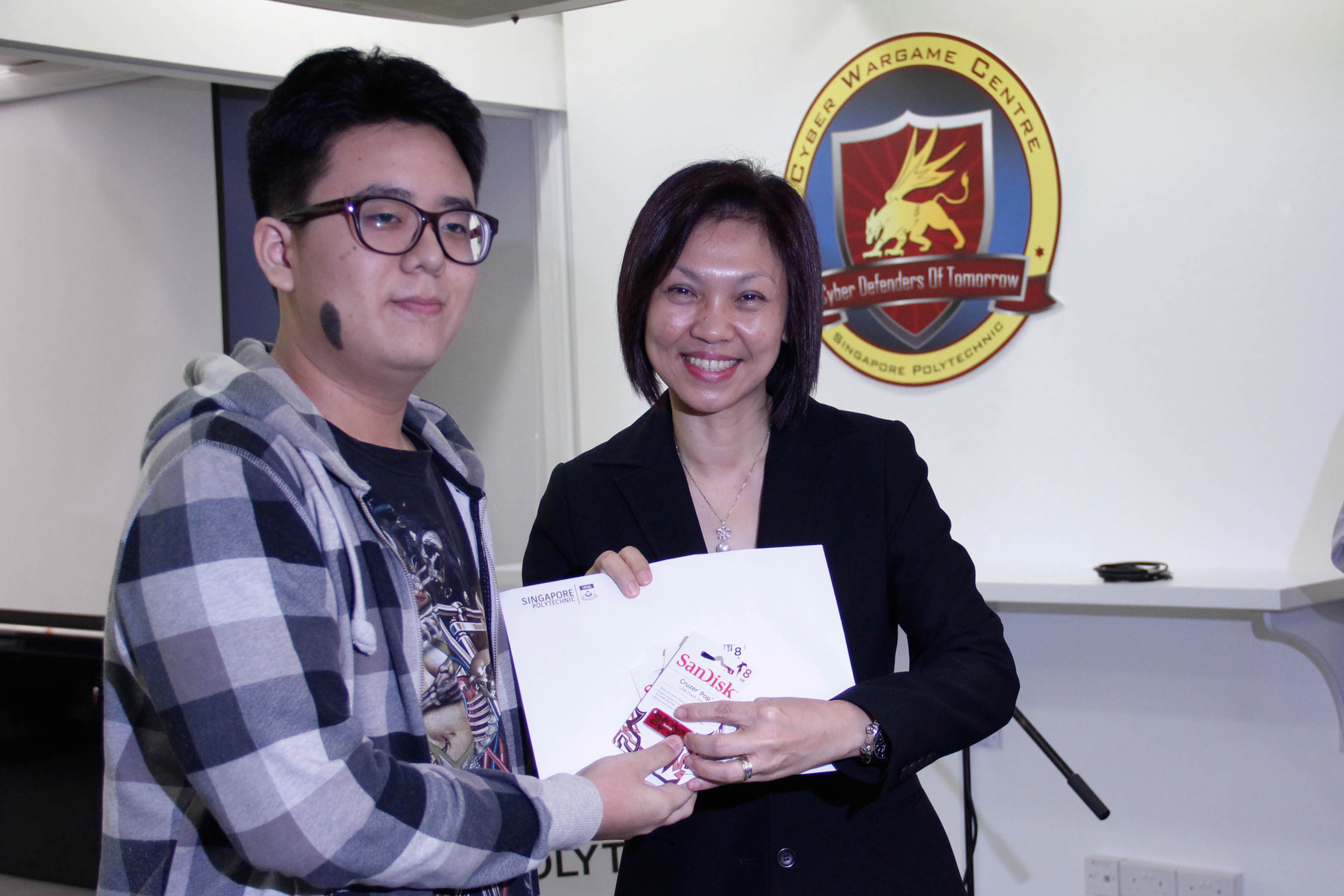 DMIT Director Ms Georgina Phua presenting Certificate of Merit to DISM CTF S1 1st Runner-up team and Top Team in July Team HBE
