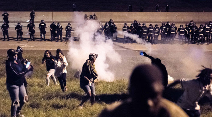 CHARLOTTE, NC - SEPTEMBER 21: Protestors run from a gas canister after blocking traffic on the I-85 (Interstate 85) during protests in the early hours of September 21, 2016 in Charlotte, North Carolina. The protests began last night, following the fatal shooting of 43-year-old Keith Lamont Scott by a police officer at an apartment complex near UNC Charlotte. (Photo by Sean Rayford/Getty Images)